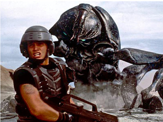 Is Starship Troopers a trenchant war parable for 2010, a cheesy excuse for coed showers, or both?