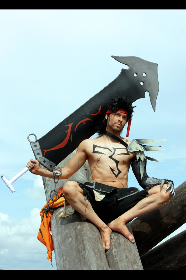 A Shirtless Man Holding Large, Pointy Objects