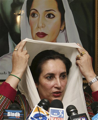 Benazir Bhutto Adjusts Scarf In Front Of Own Likeness