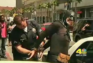 Cops handcuff Batman, drag him away to jail