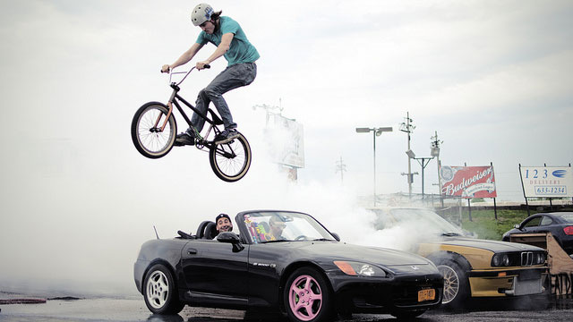 Watch a bike jump a GT-R-powered BMW doing a burnout